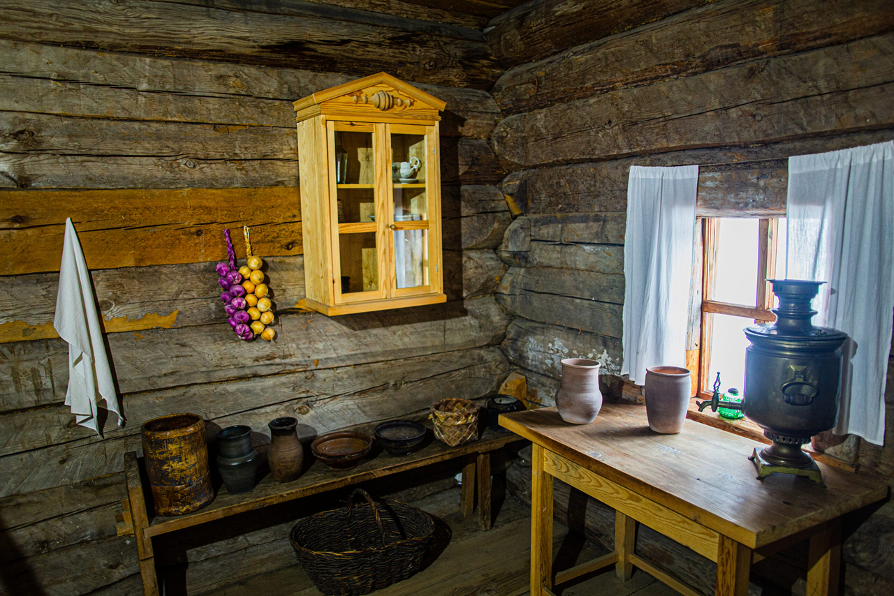 Interior of an old Russian wooden house, old wooden furniture and pottery for cooking, samovar