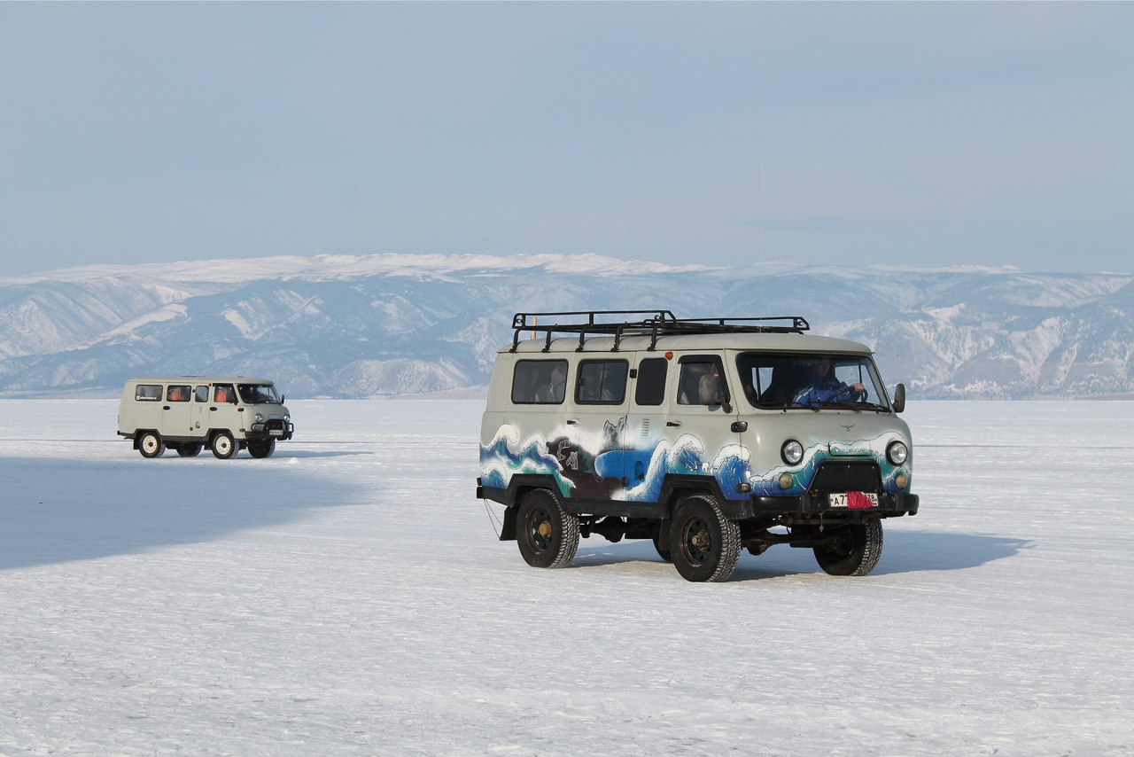 UAZ vans on the frozen lake covered with snow, UAZ van with sea painted on it