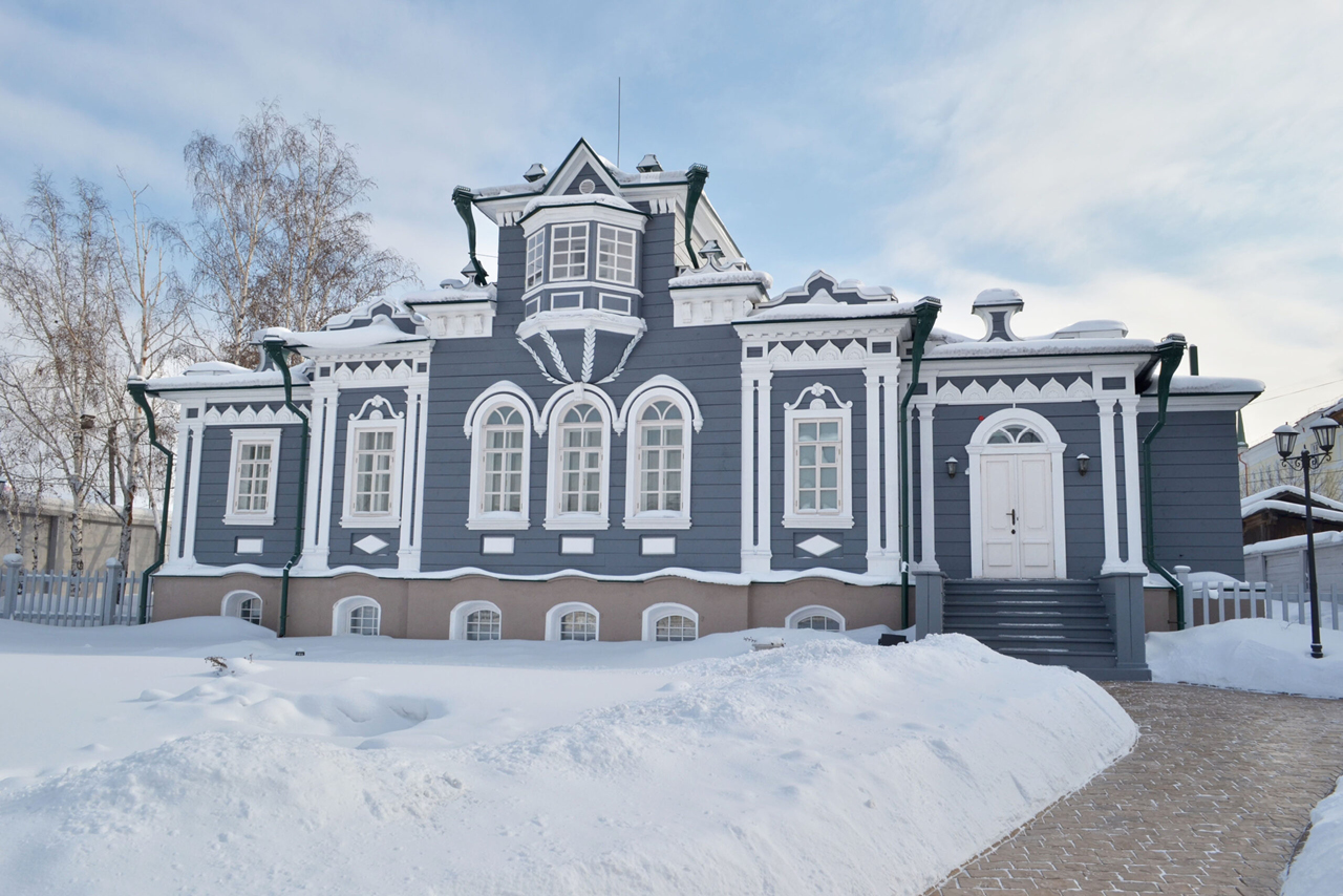 A grey and white wooden house built in the style of classical noble mansions decorated with a bay-window in winter