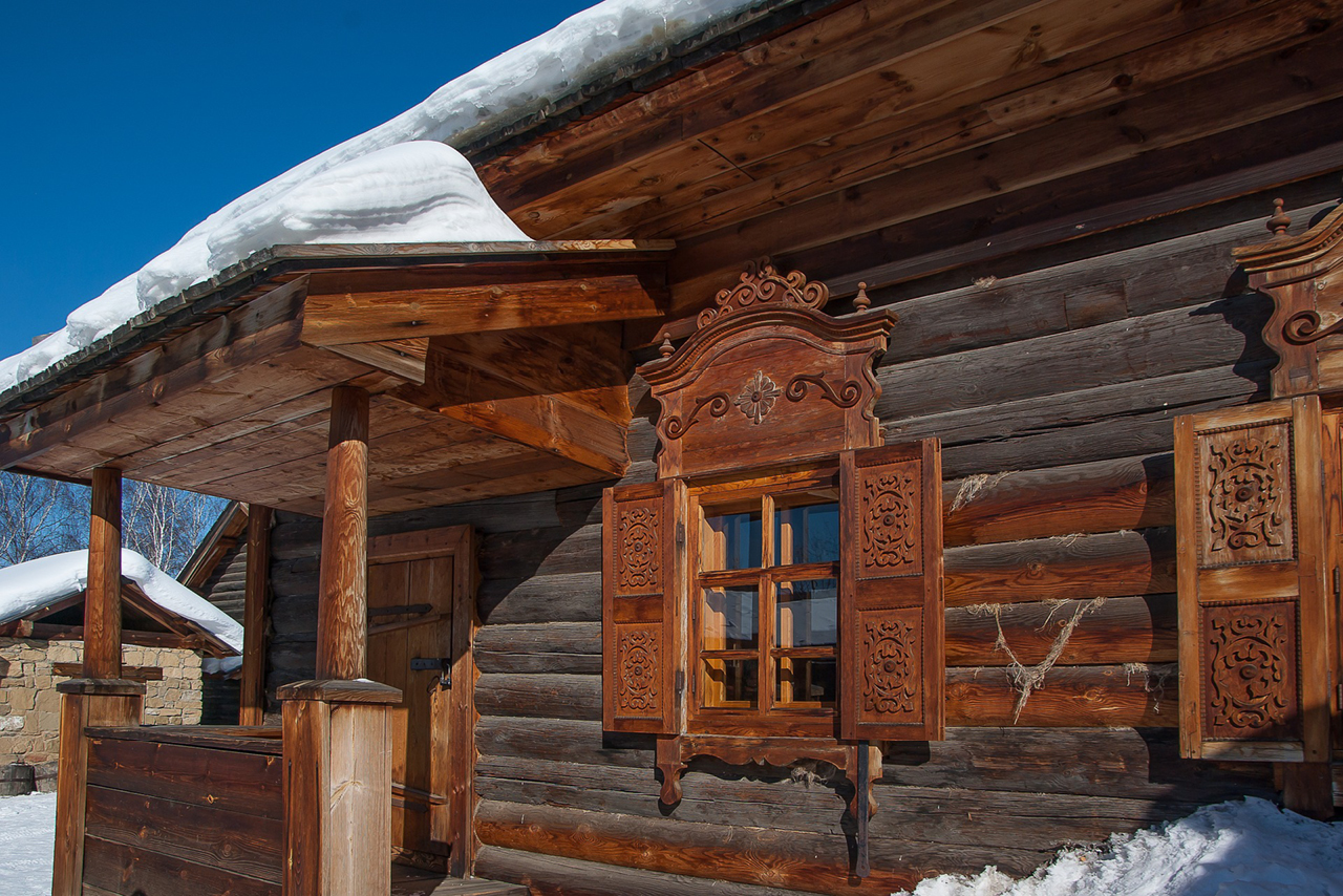Russian wooden house with storm shutters in winter, snow on the roof of a wooden house.