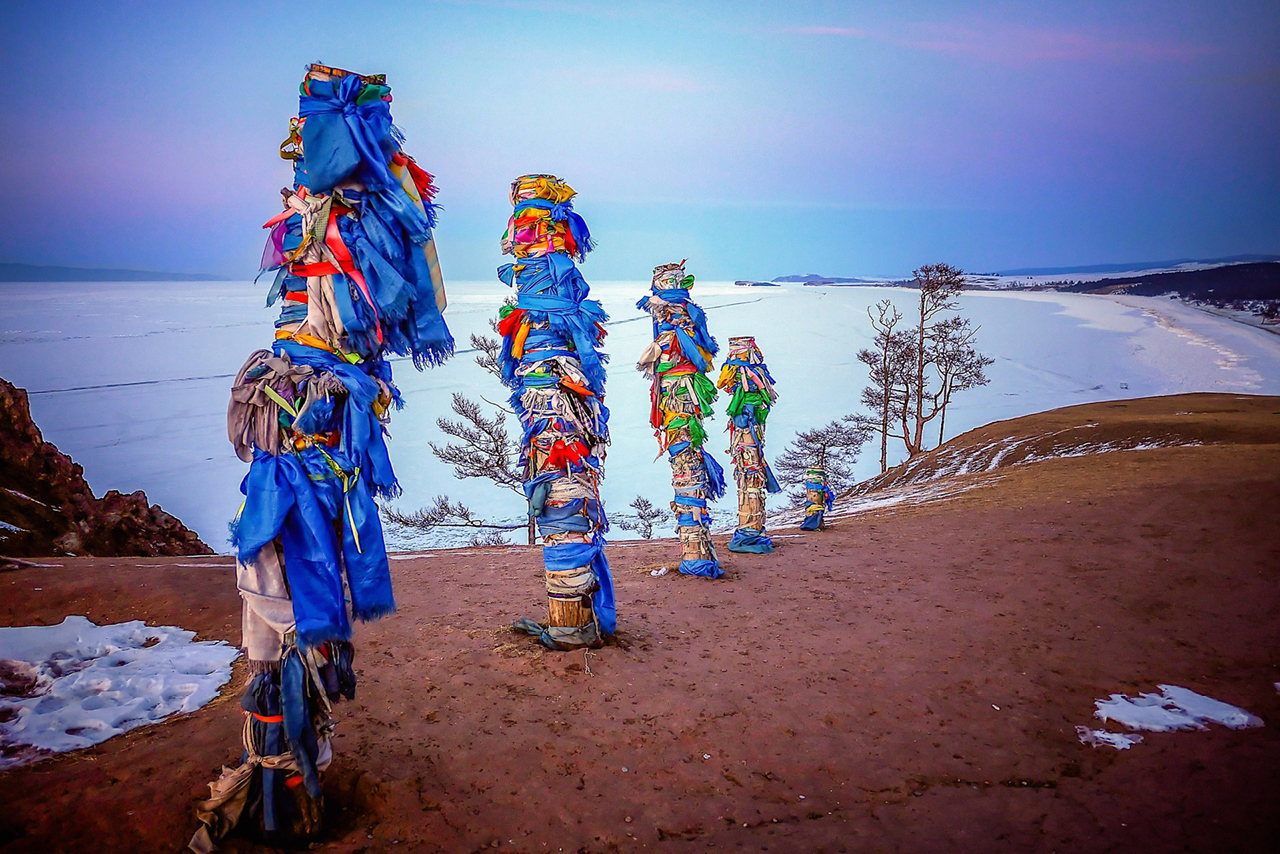 Several sacred piles decorated with colorful ribbons on a shore of a lake