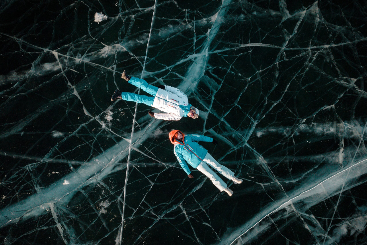 Two people laying on the ice of a lake