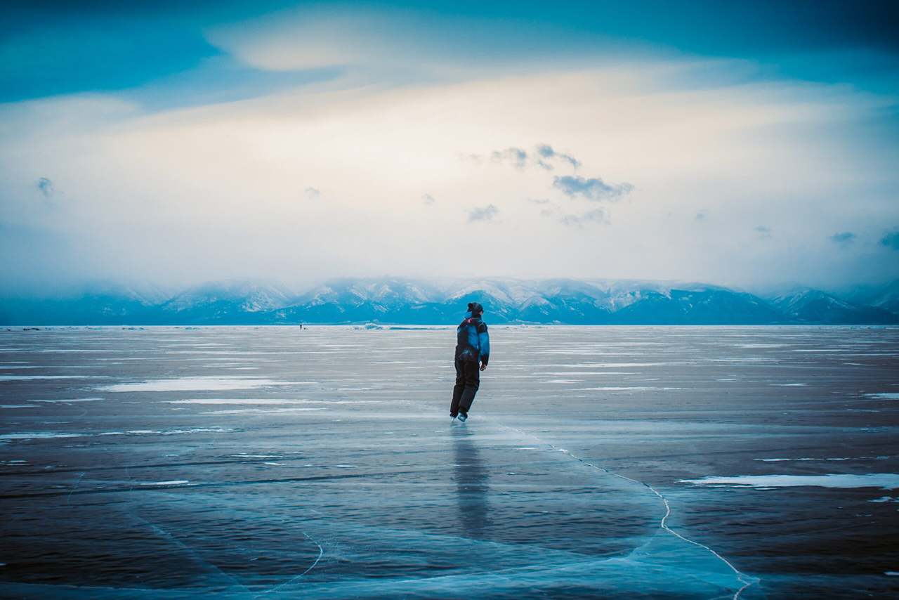 A person ice skating on an endless frozen lake