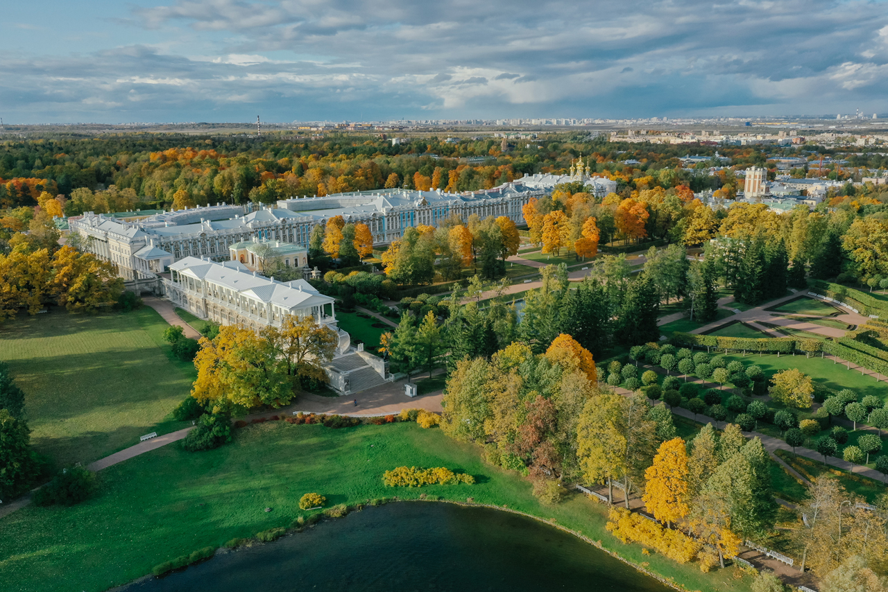 Aerial view of a blue royal palace surrounded with a park in autumn