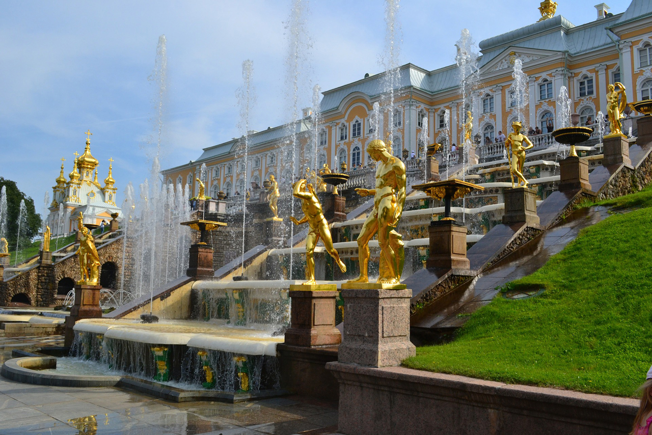 A yellow classical palace with white columns, grand cascade of fountains in front of the palace, fountains decorated with golden statues along the staircase, archway of grotto in the middle of construction, beautiful royal palace