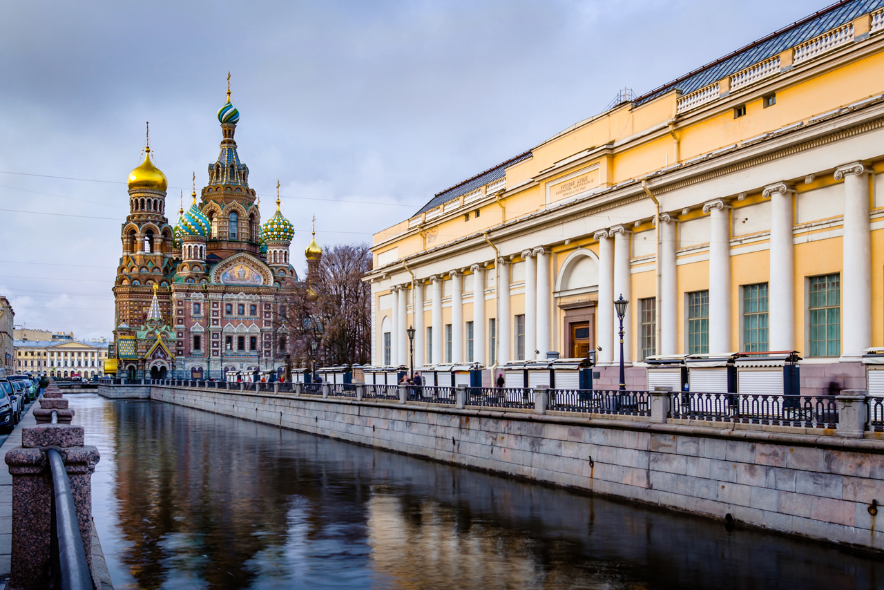 A yellow classical building and a colorful cathedral on an embankment