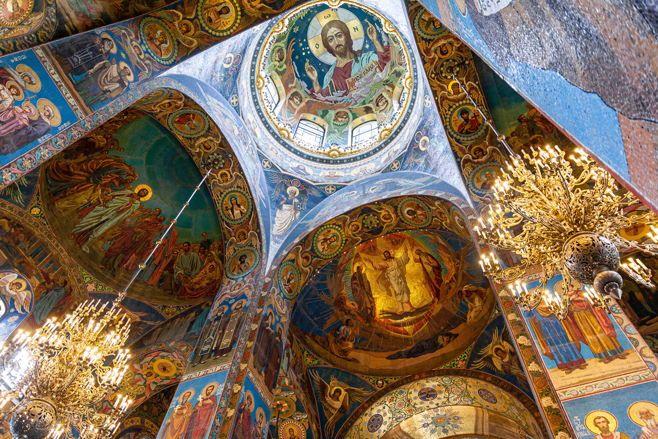 Colorful mosaic decoration of a church interior, image of a Jesus the Christ inside of the main dome, cathedral decorated with gold