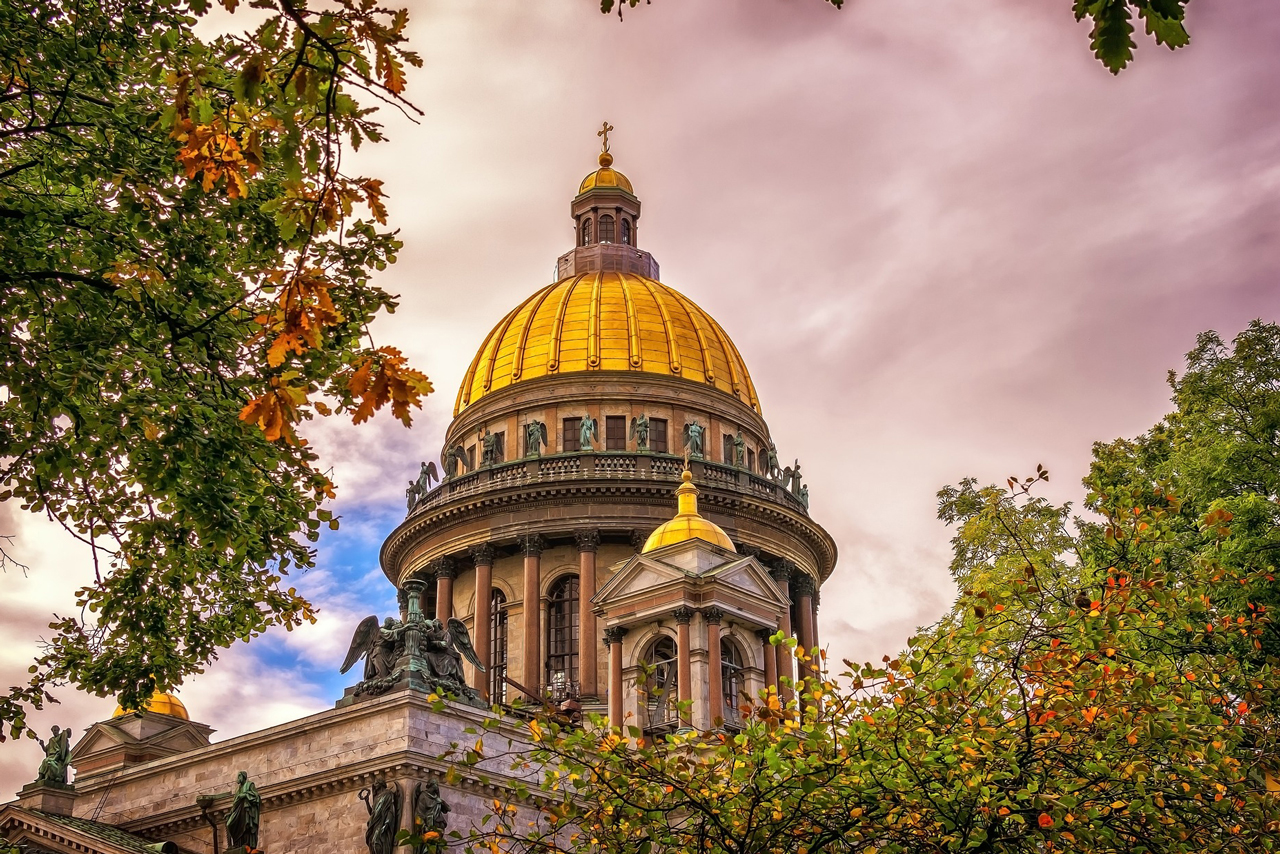 A magnificent cathedral with a large central dome and four subsidiary domes in neoclassical style, cathedral faced with gray and pink stone, features red granite columns with Corinthian capitals, statues on the roof of the cathedral