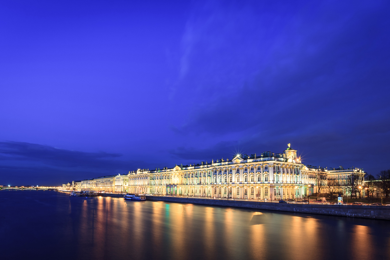 A beautiful royal palace on the embankment illuminated at night, a baroque palace in Russia
