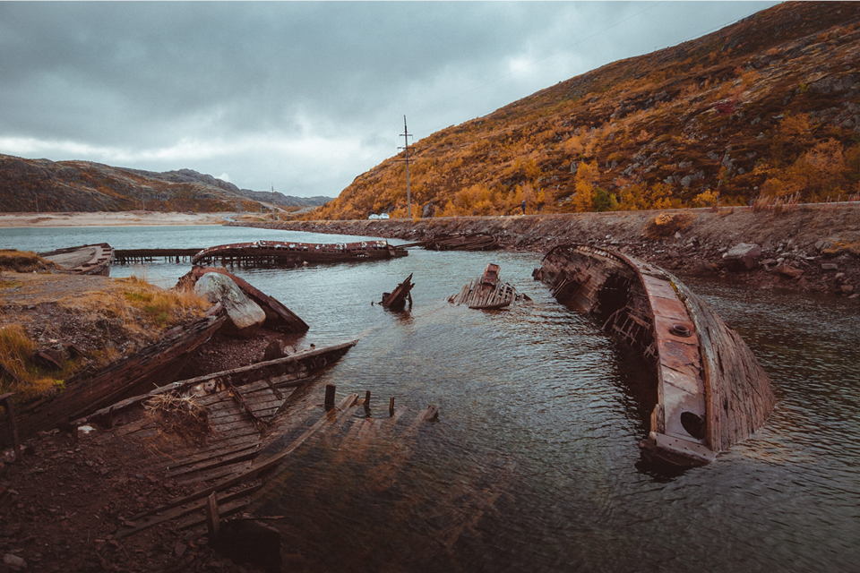 Pieces of old broken fishing boats in water, hill with yellow grass behind it