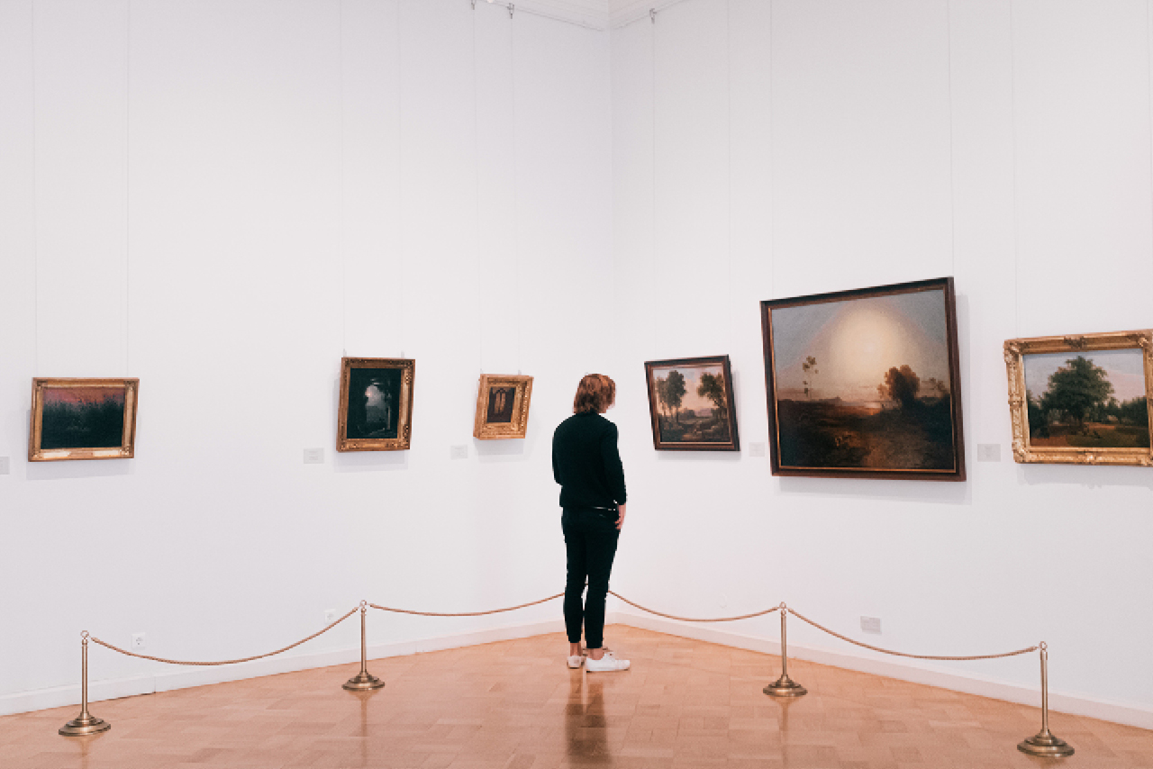 A person in a museum, landscape paintings in a museum