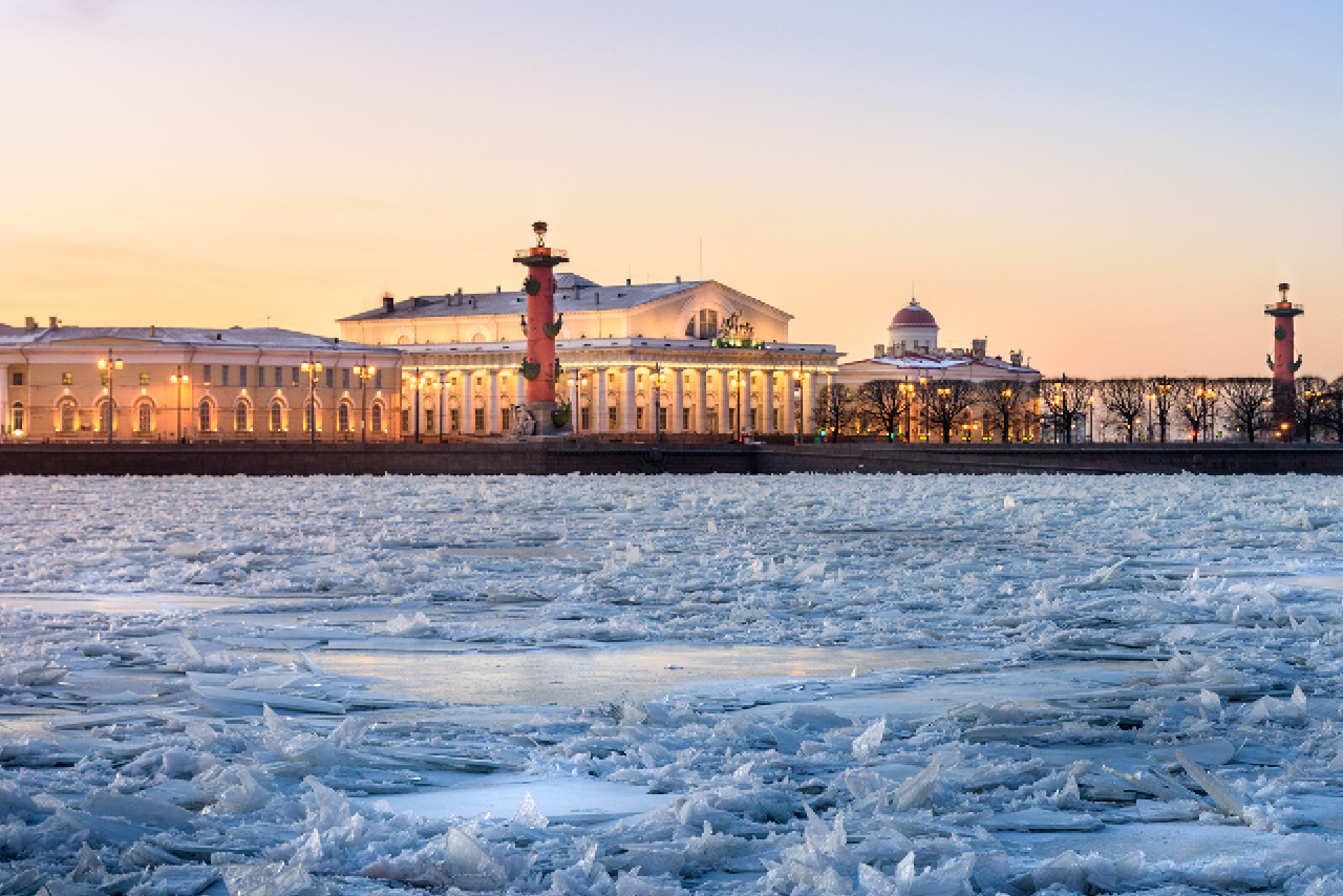 Beautiful buildings of a big city on the river bank in the evening, old stock exchange building with colonnade looking like a greek temple, Rostral Columns (red victory columns with parts of vessels inside), the frozen Neva river in winter