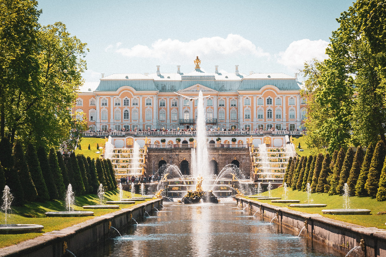 A canal with fountain in front of a beautiful royal palace, yellow palace in baroque style, staircase and cascade of the fountains with gilded statues in front of the palace