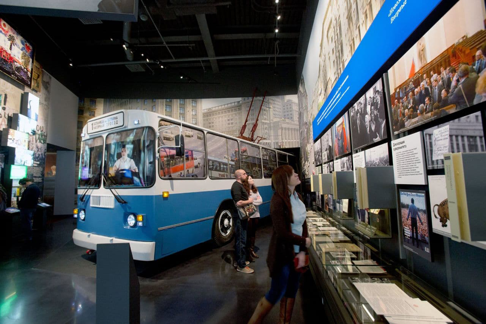 A museum room with a retro bus inside, two visitors of a museum look at the pictures on the wall