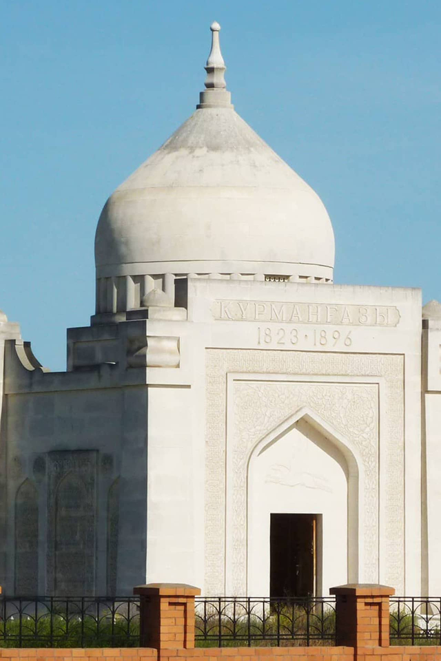A white building with round white dome and decorations in Mideast style, a name in Cyrillic letters carved in white stone