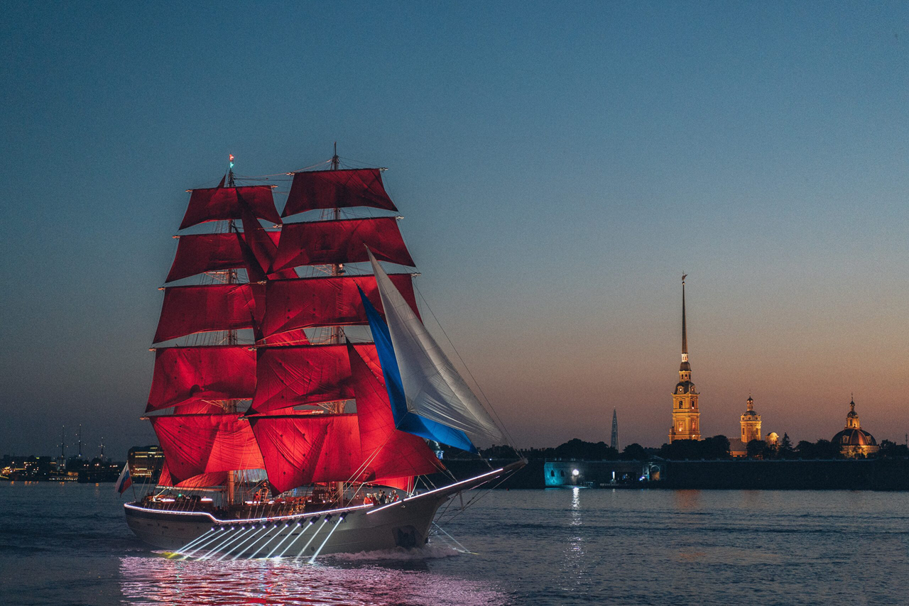 A boat with red sails on the water late in the evening, a tall illuminated tower on the other side of the river, beautiful city at night
