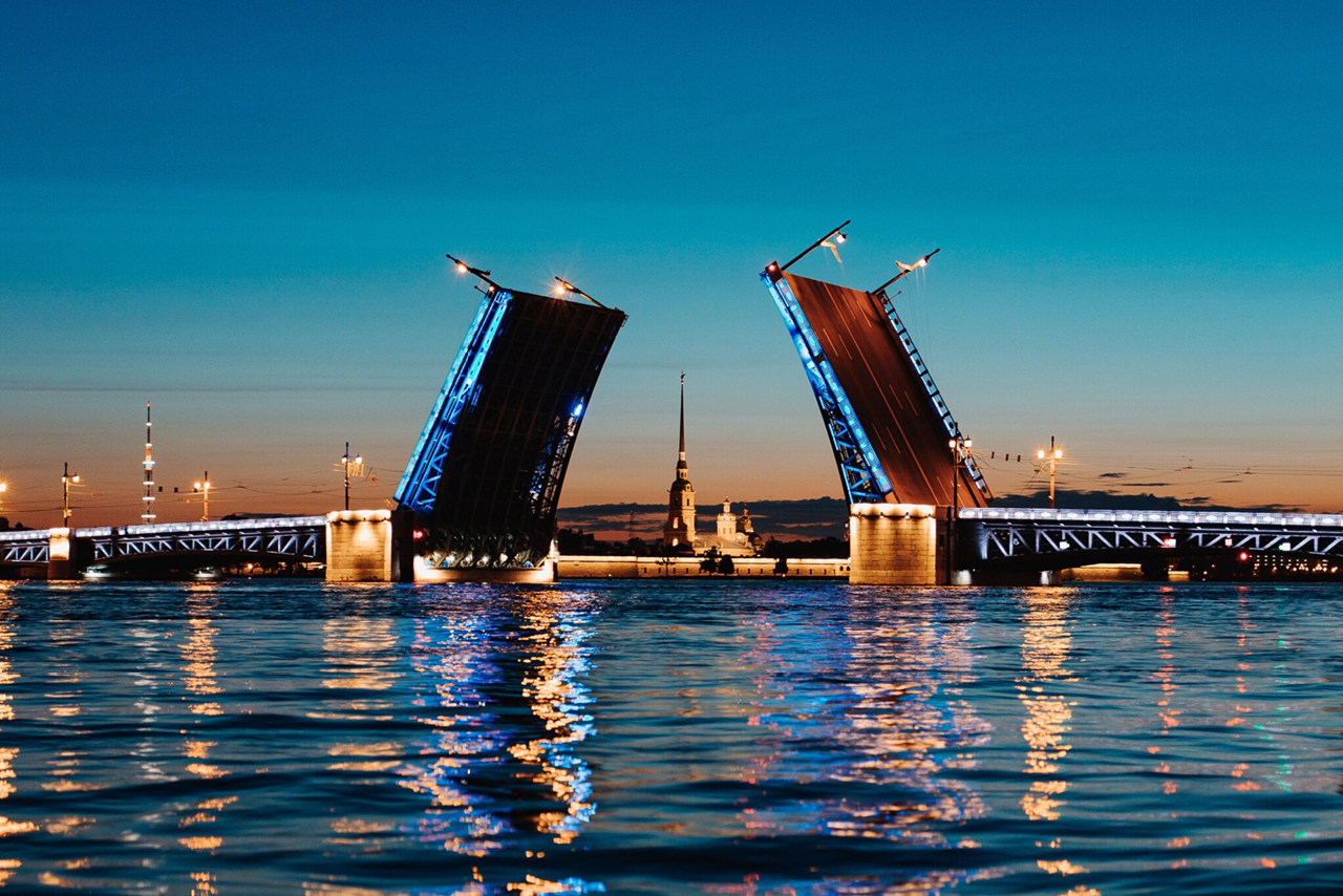Two lifted parts of a bridge at night, river, illuminated city at night