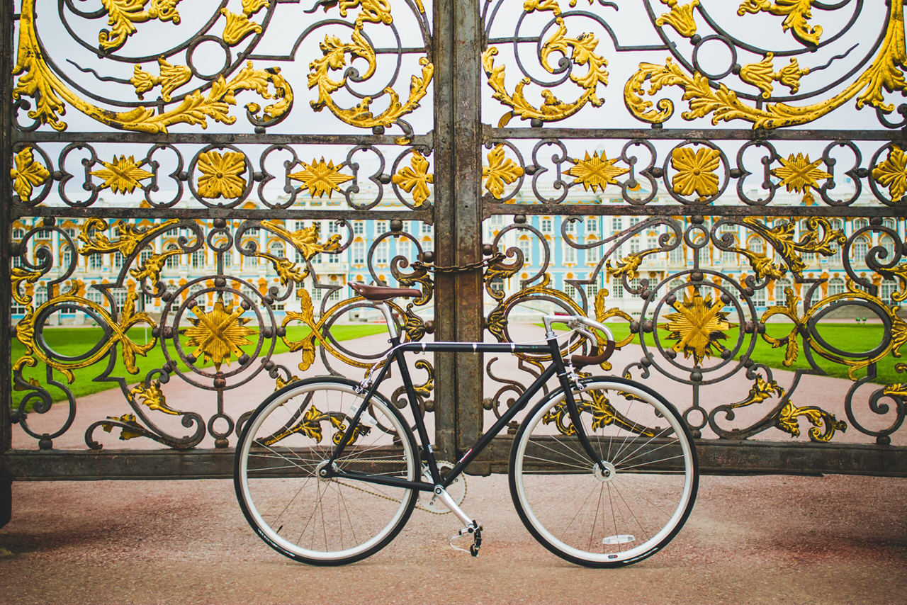 A bicycle next to the wrought iron gate with gilded elements in front of a palace