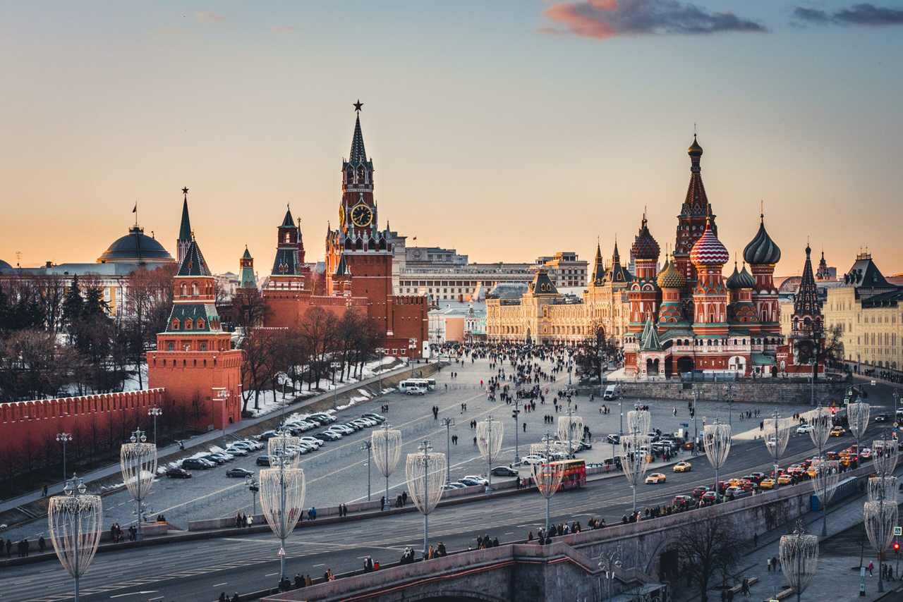 Historical place of a city and a large road with intensive traffic in front of it, on the left a red fortress with towers, the tallest tower with clock and a star on the top a spherical roof of a palace behind the fortress wall , a colorful cathedral on the right