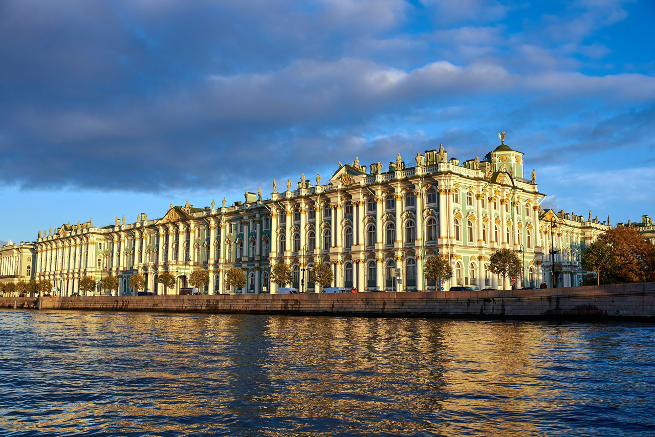 A beautiful royal palace on the embankment, a green baroque palace with sculptures on the top, river in front of the palace