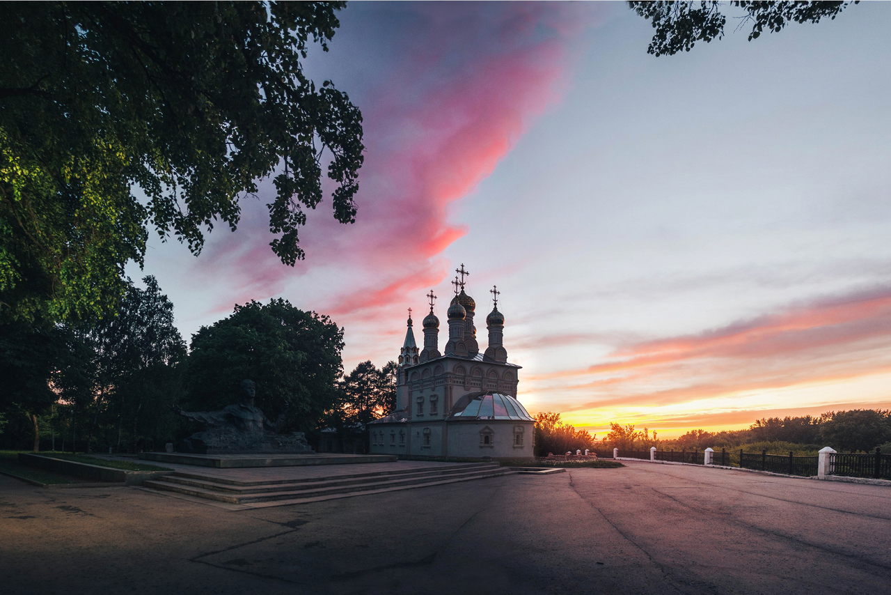 A memorial with a bronze sculpture of a top part of man's body near a white orthodox cathedral during the sunset, a fence on the right