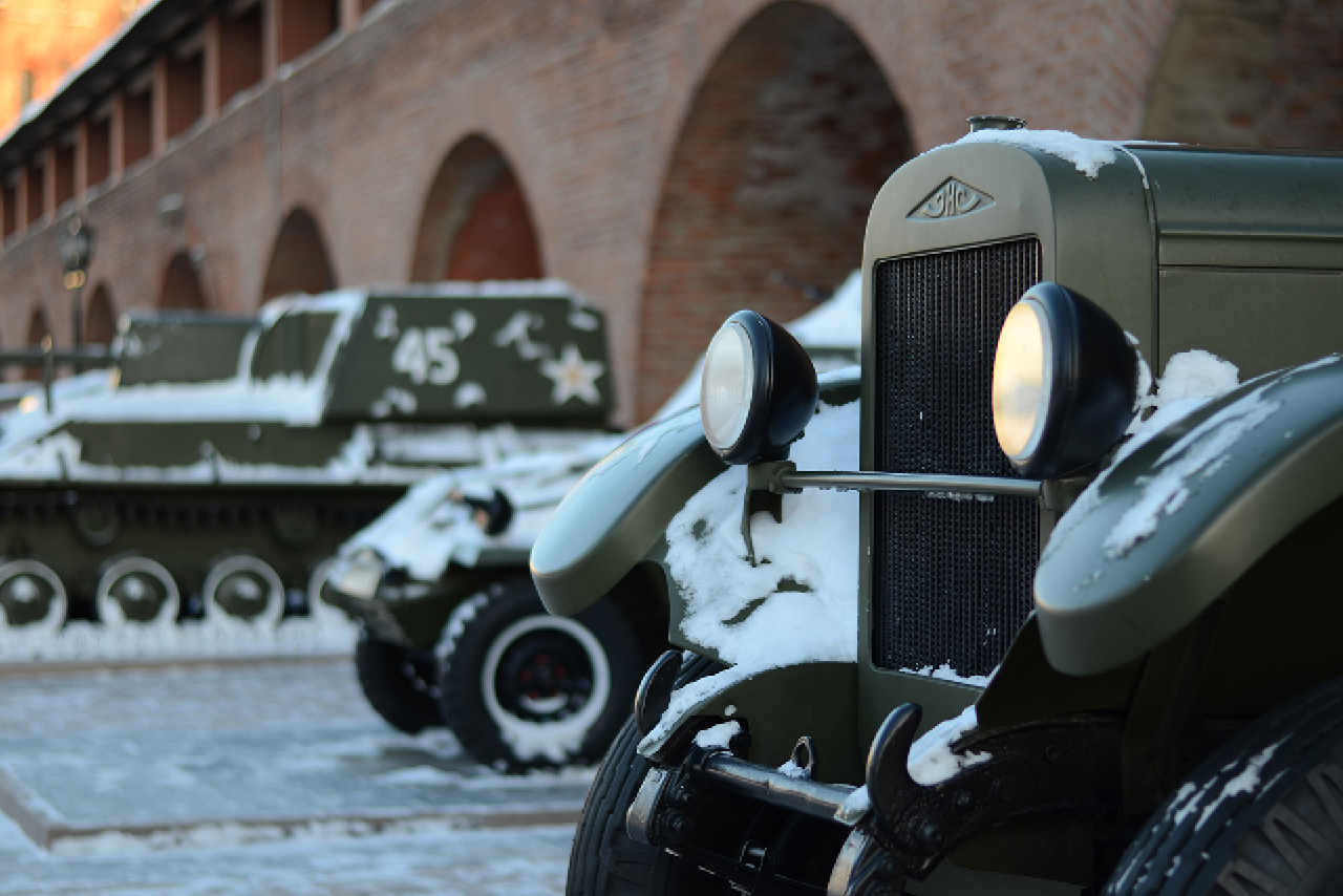 A front part of a retro military car in front, other military cars and tanks behind, a red brick wall with arches in the background