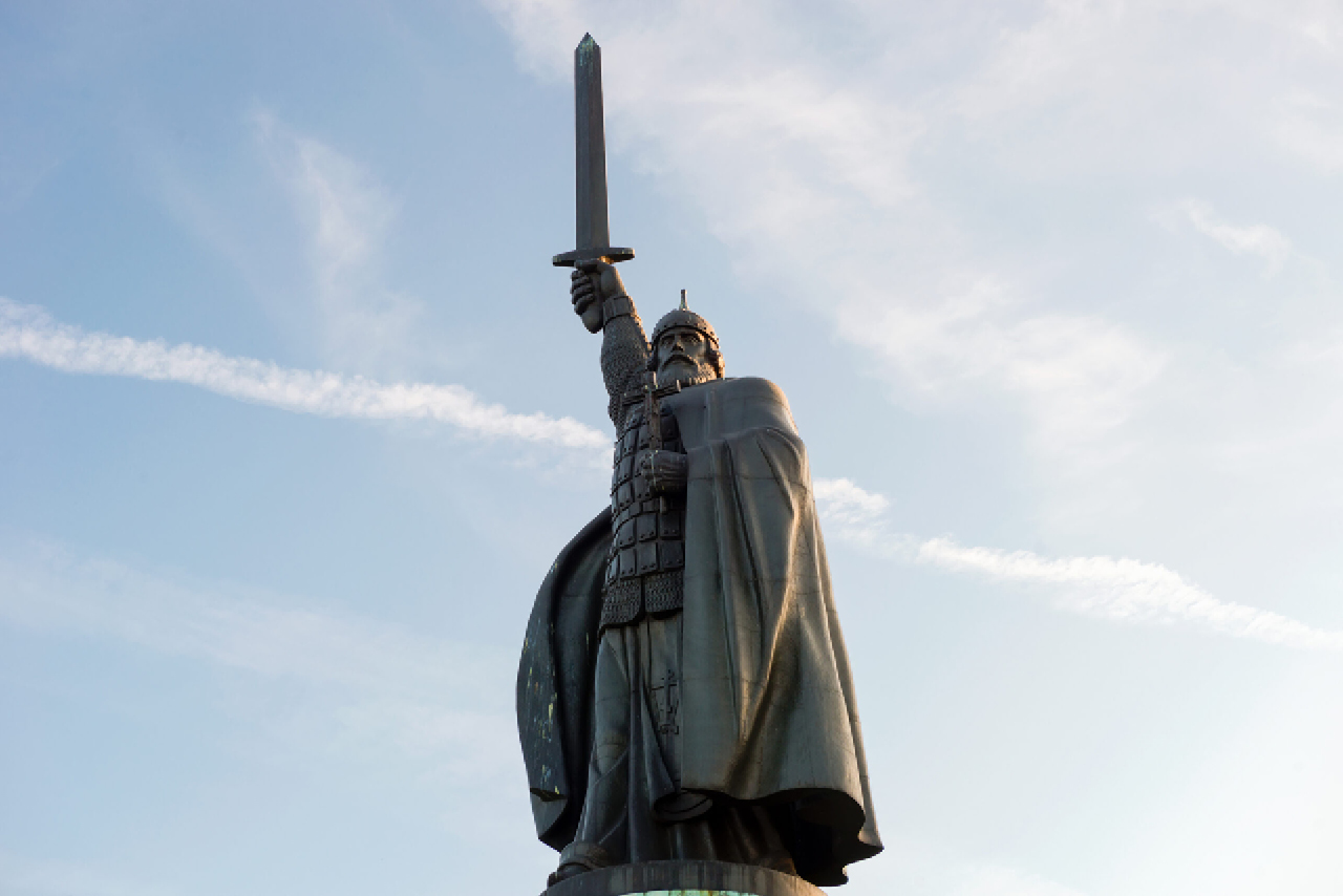 A monument of a Russian knight wearing chain armor and a cape, with a hand with a sword lifted up to the sky