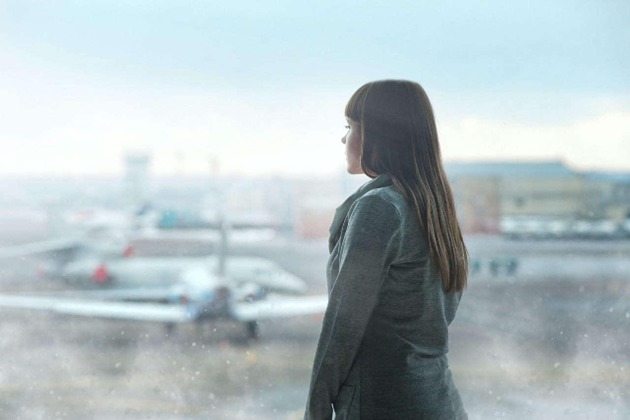 A lady at the airport in front of a large window with a view to the airplanes